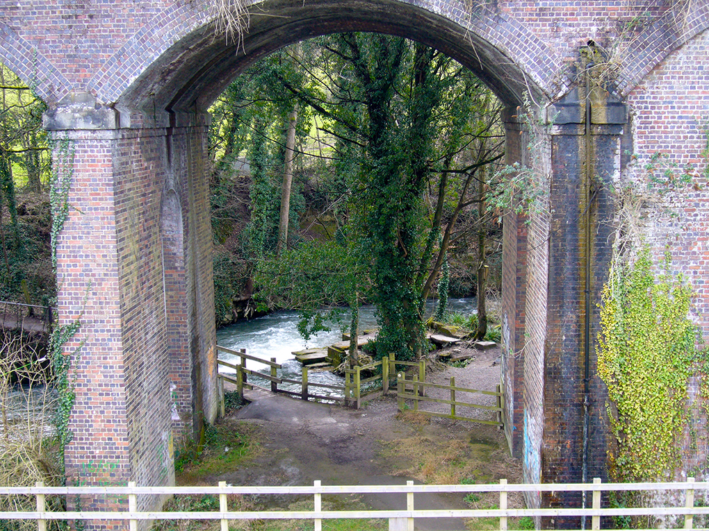 view of a river through railway arches