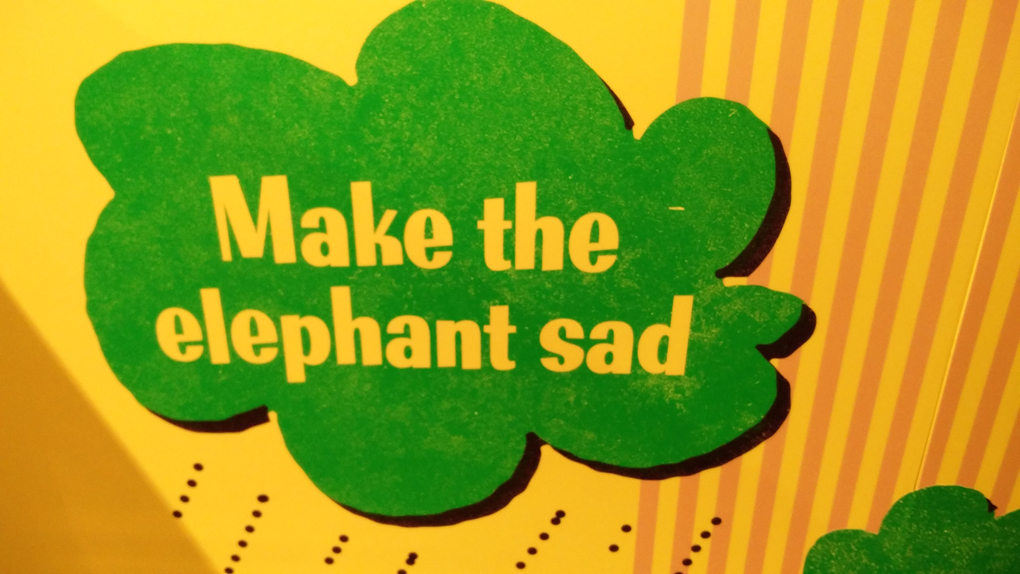 sign reading make the elephant sad