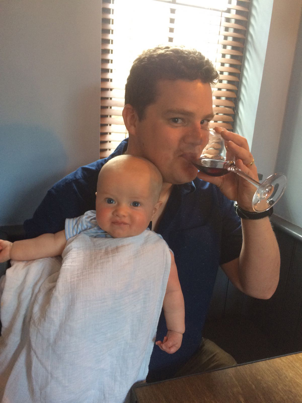 man drinking wine with baby