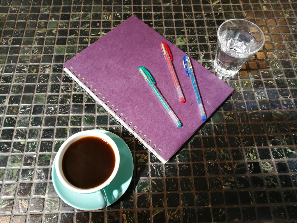 pen, notebook and coffee on a table