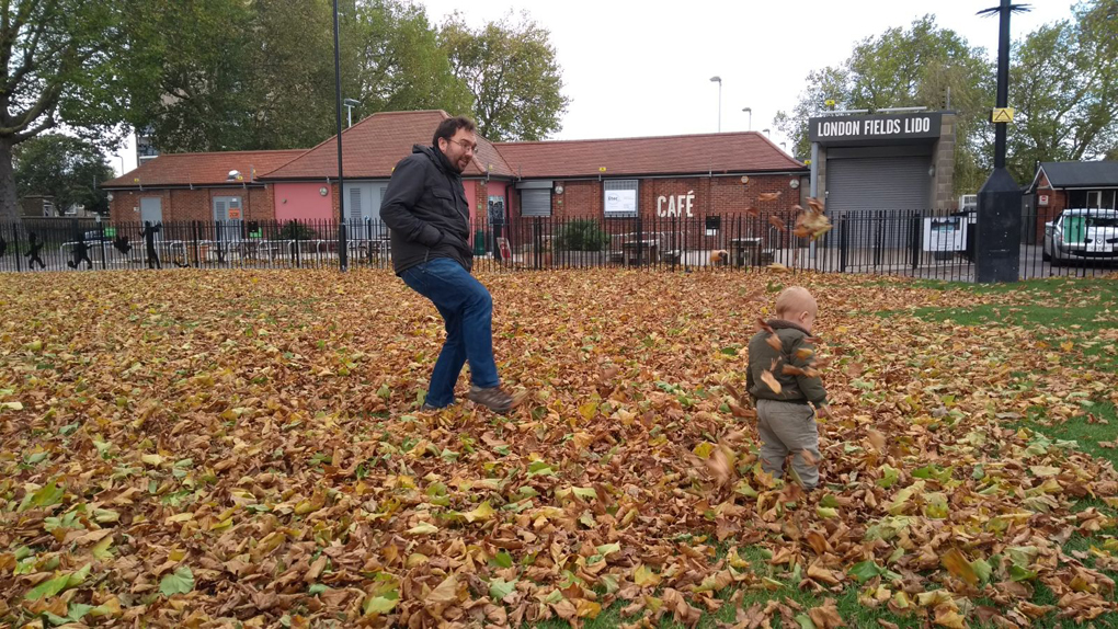 man and toddler playing in fallen leaves