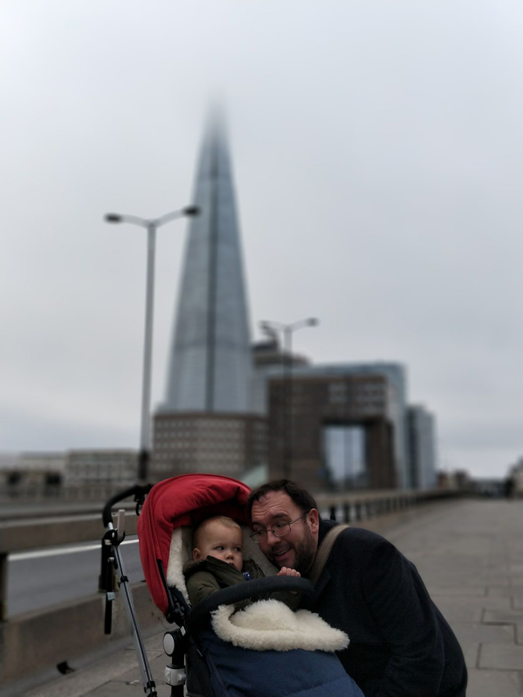man and baby in front of the Shard