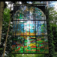 stained glass window hanging in forest
