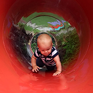 baby crawling through red tunnel