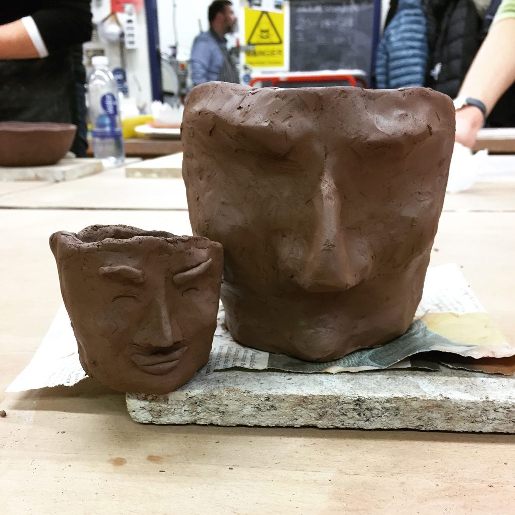 Two unfired clay pots with partially-sculpted human faces on them