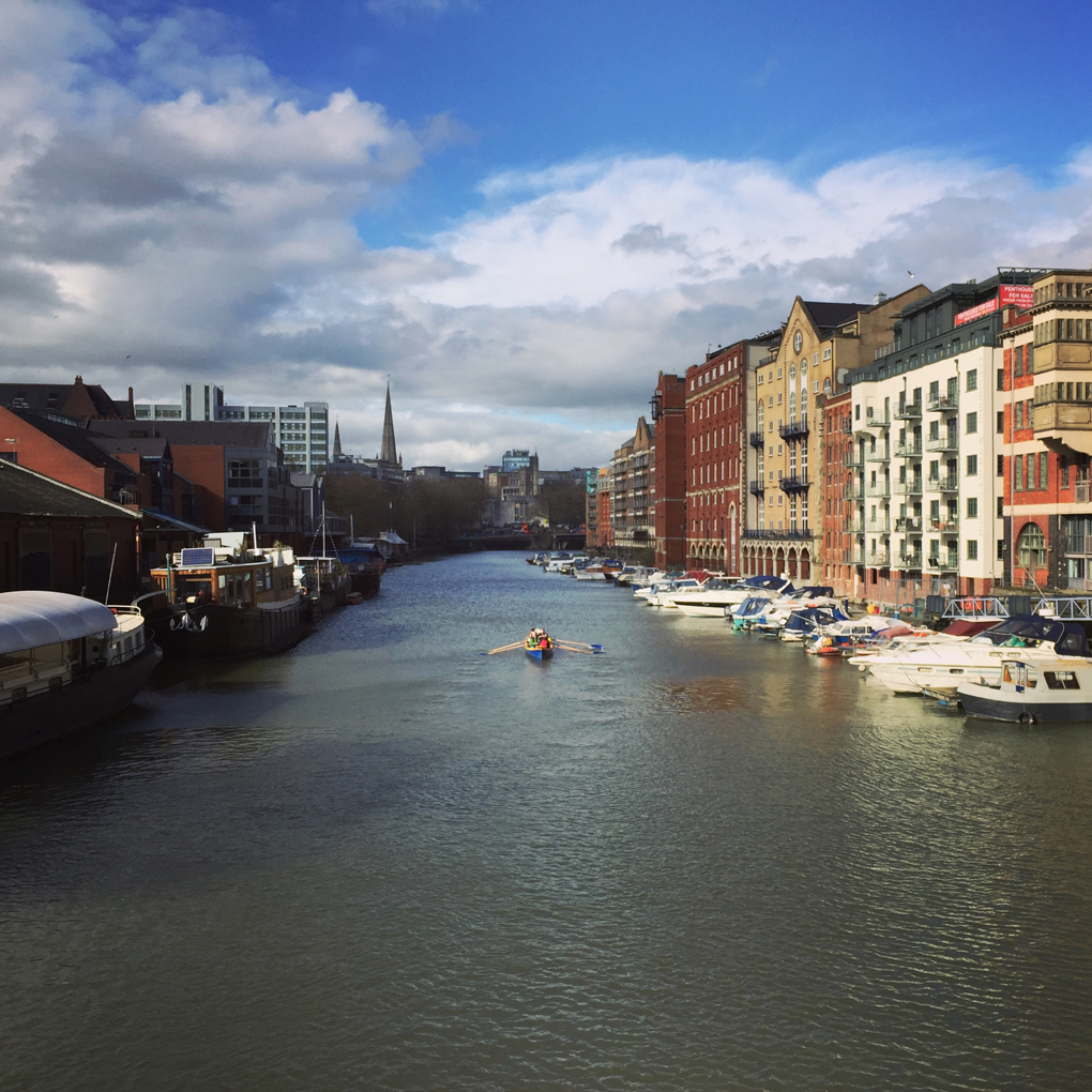View of the river in Bristol, with buildings and boats on either side and a rowboat in the middle. Sunlight is hitting the water but there are clouds too.