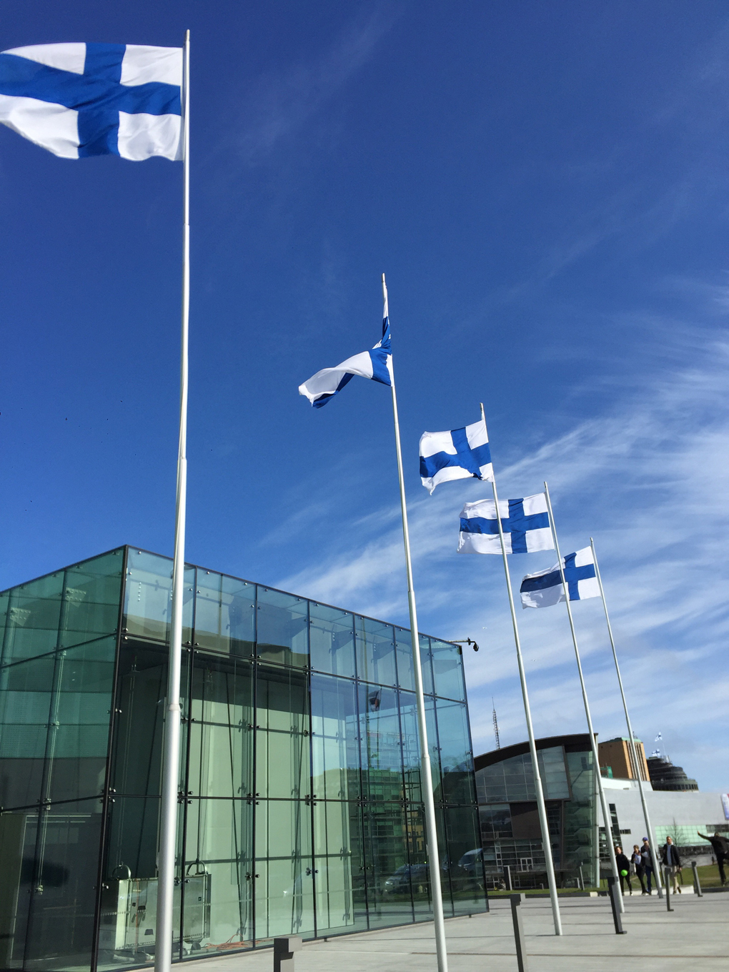 Finnish flags in a row outside a modern building