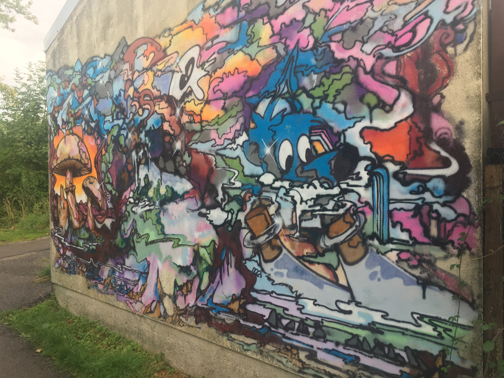 Colorful graffiti featuring a blue skinned character