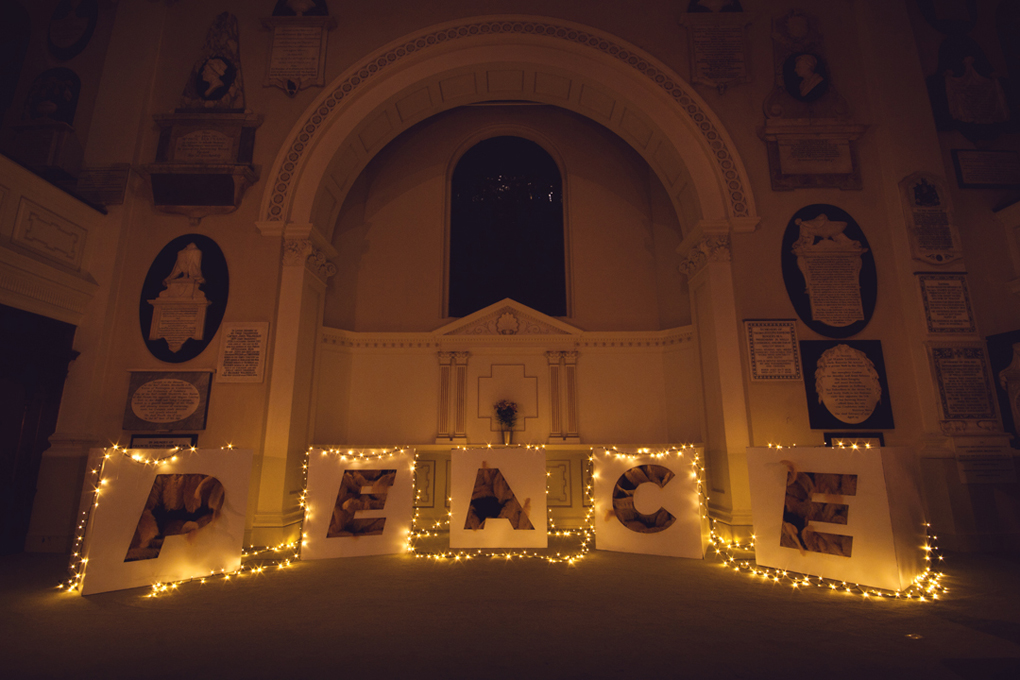 Art installation of golden feathers spelling out the word 'Peace' in St Swithin's Church in Bath.