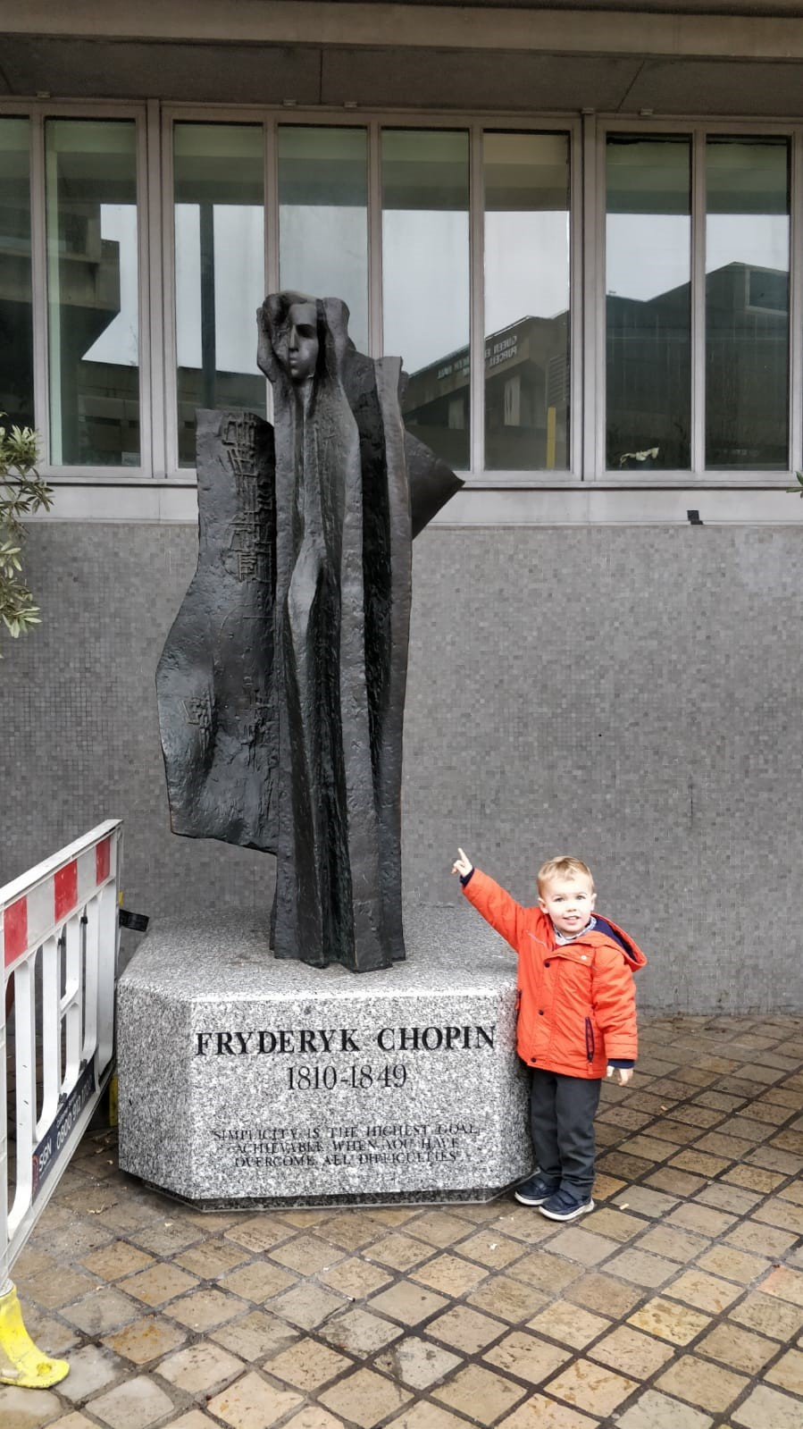 small boy pointing at statue of Chopin