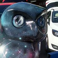 A giant model of an owl painted with the cosmos in a car dealership forecourt.