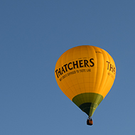 This is a photo of a hot air balloon with the Thatcher's cider branding on it. The balloon is yellow and green in a cloudless sky.