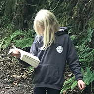girl reading a book while walking through a wood
