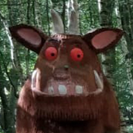 A small boy stands in a woodland area, near a carved statue of the Gruffalo.