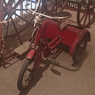 A sweet collection of antiquarian bikes consisting of a Penny Farthing, a large Victorian tricycle with a huge front wheel, a child's tricycle and a child's scooter, nestled in a corner of the Athelstan Museum in the lovely old town of Malmesbury.