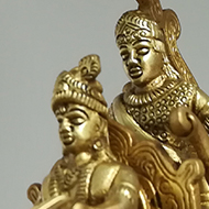 A golden statue of what I assume is Krishna, Arjuna and Hanuman, from the Mahabharata.