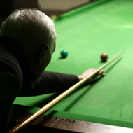 man playing snooker shot over his shoulder