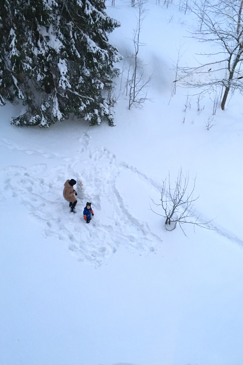 Aerial view of an adult and a child building a snowman