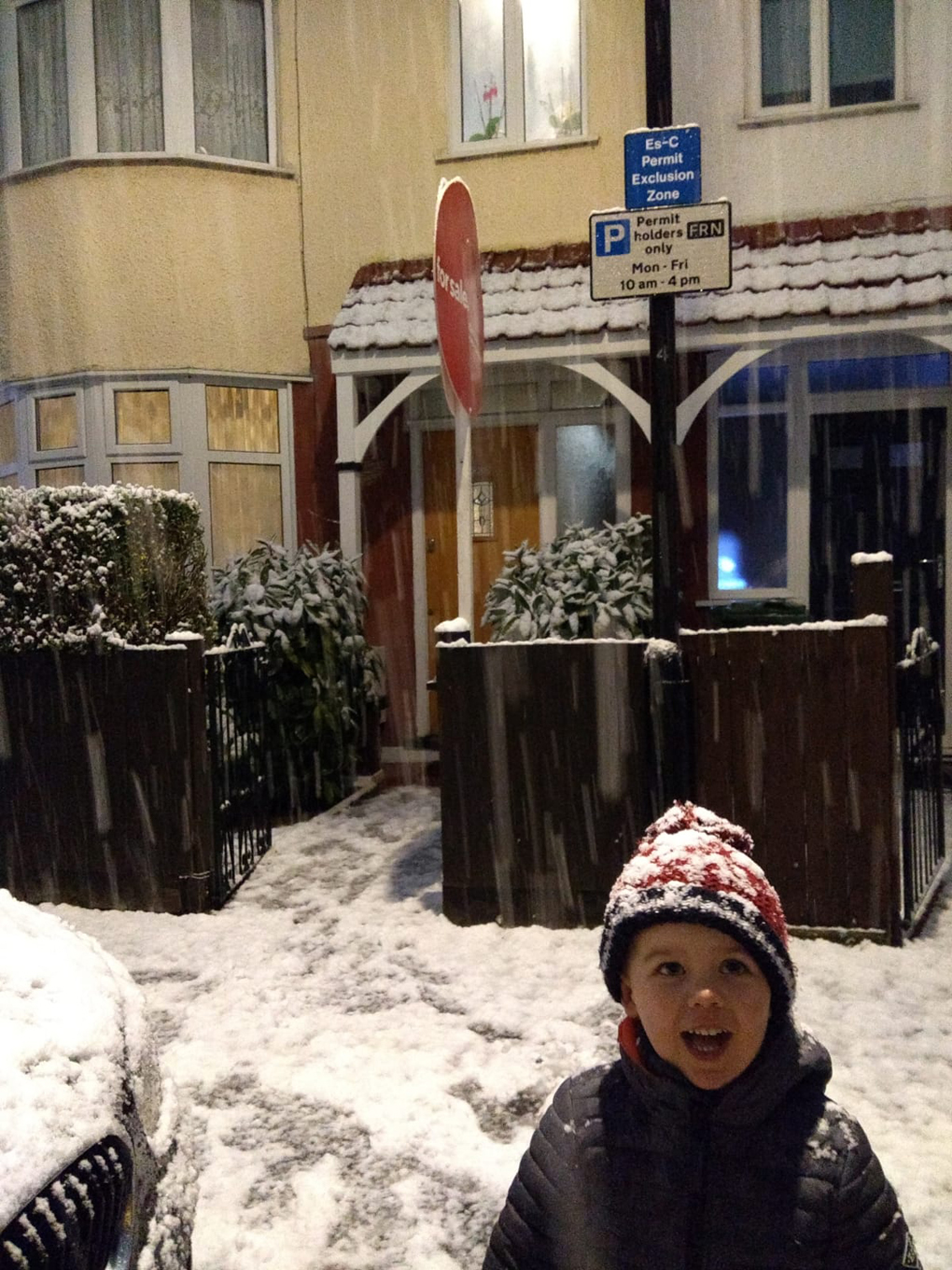 child outside a house in a snowy London street