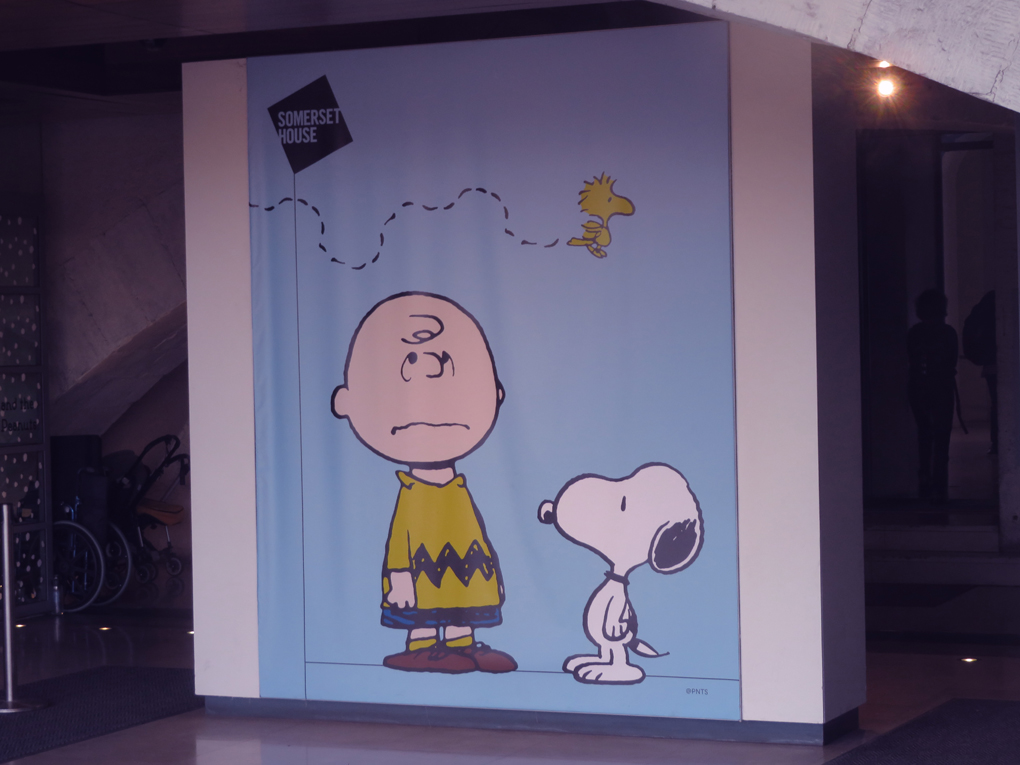 The picture is of a large poster featuring Charlie Brown, Snoopy and Woody from the Peanuts cartoon outside the exhibition entrance at Somerset House