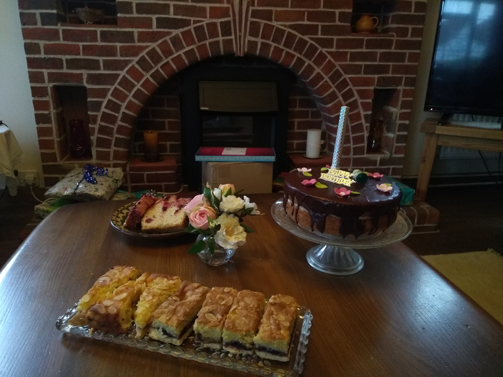 Table in front of fireplace with cakes on top, including birthday cake with unlit firework type candle