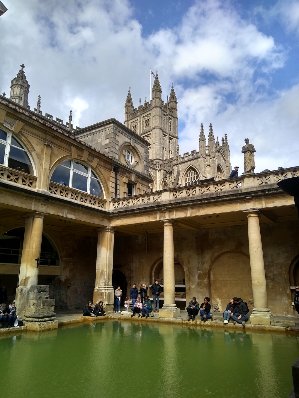 The inside of the Roman baths with Bath abbey behind