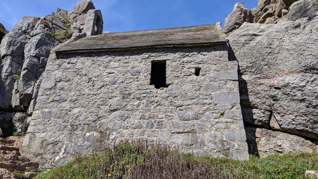 A small stone chapel built into a cliff face.