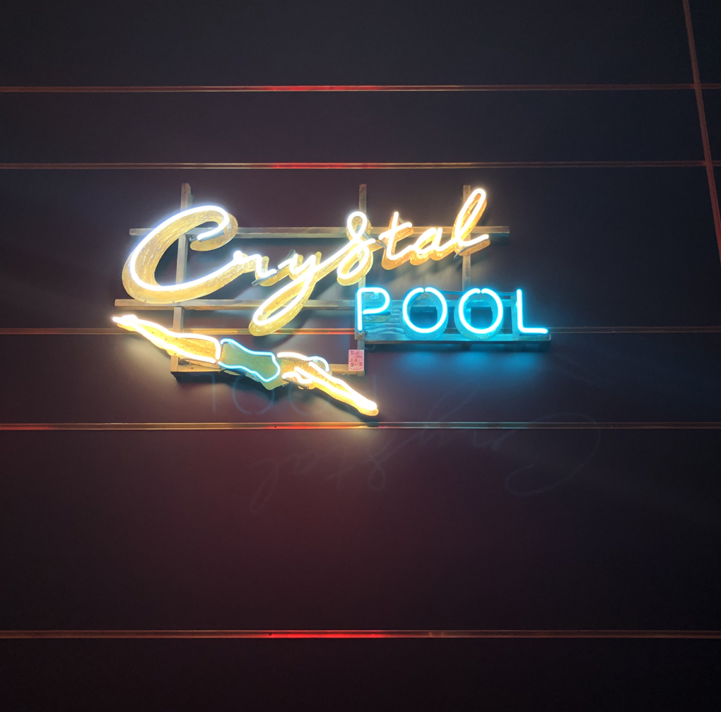 Neon sign of crystal pool with swimmer