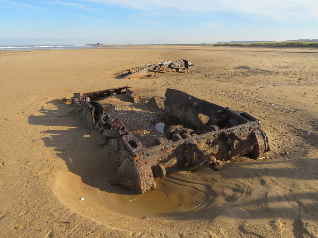 we see the rusting hulls of two WW2 Covenanter tanks half buried in the sand on the beach at Titchwell North Norfolk, with the sand in the background