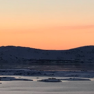 Sunrise over a flat landscape of snow and lakes with small mountains in the distance