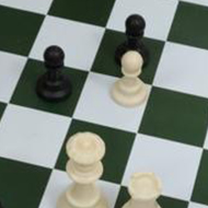 A chess game in its late stage viewed from above. The board is on a table in an office lunch area.