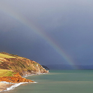 A faint rainbow emerging from a dark sea, curving inland over brightly-lit cliffs and coastal fields