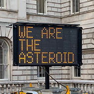A dot-matrix roadworks sign displaying the slogan 'We are the asteroid'