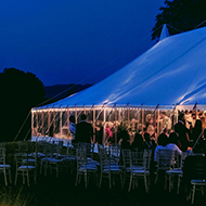Wedding reception in field; lights and marquee