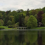 View across a still lake, with many different coloured trees surrounding an ornate bridge in the background, and a cloudy sky above