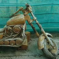A crazy and brilliantly made Easy Rider motorbike with extended forks, parked in a quirky garden centre, looking a bit worse for wear, needing a bit of a refurb - all cleverly made of wood but not for sale!