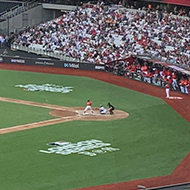 A view of a baseball match from the stands. The stadium is big and relatively full.