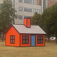 A 3-D model of a cartoon house on an otherwise empty field in a built-up area.