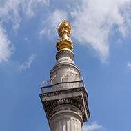 The Monument to the Great Fire of London rises above narrow London streets with its golden urn high up catching the sunlight.