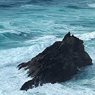 Towering, rough pillars of dark stone standing high above stormy waves