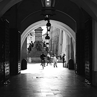Black and white photo of a man cycling through some arches in the old market square in Krakow.