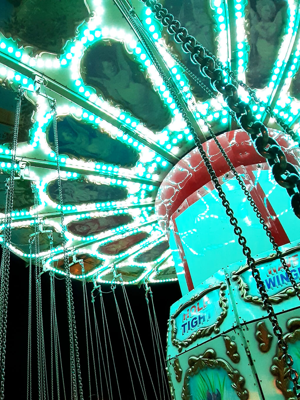 Bright lights in the canopy over a rotating swing ride, with chains to each seat hanging down into the picture