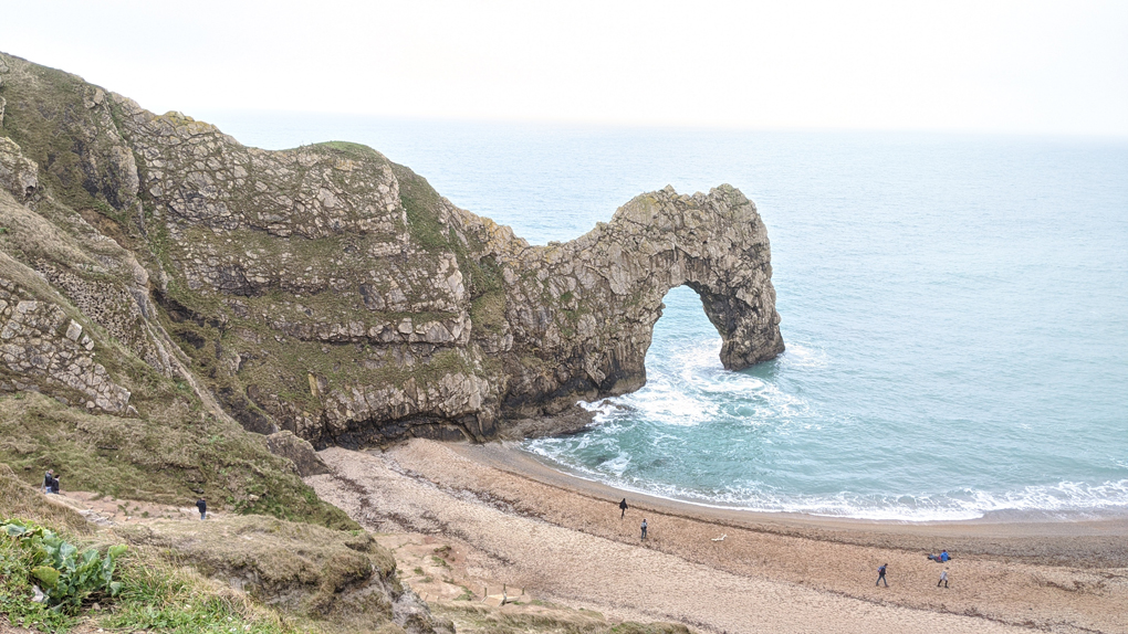 Durdle Door, a natural limestone arch, reaching out into the sea in Dorset.
