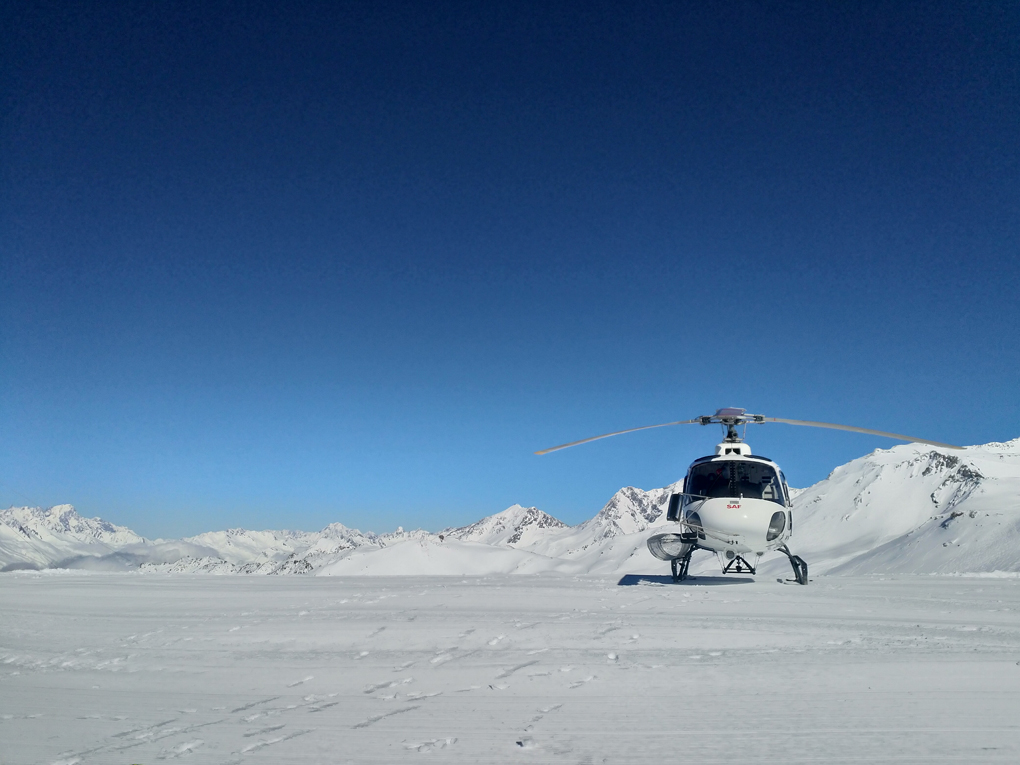 A white helicopter parked on pristine snow with empty blue skies behind it.