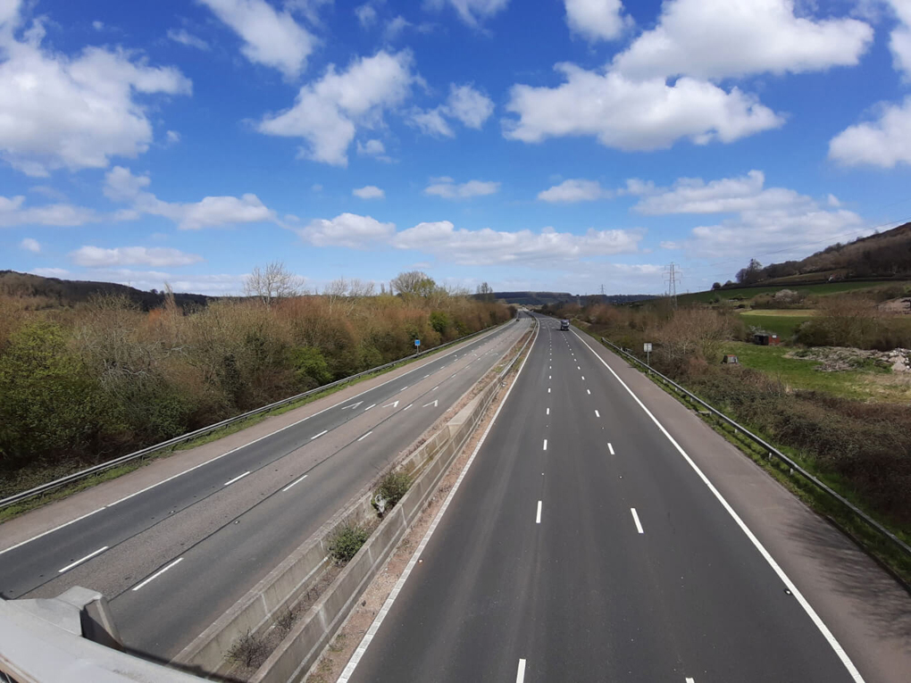 View of an English motorway banked by green hills on either side, with almost no traffic using it during the British COVID-19 lockdown in late March 2020
