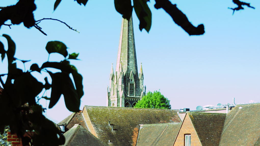 The spire of St Martin's church Dorking  is framed by rooftops on a sunny lock-down day.