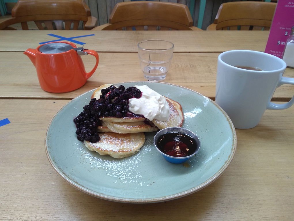 A plate of pancakes with blueberries, syrup and yogurt. Plus a pot of tea.