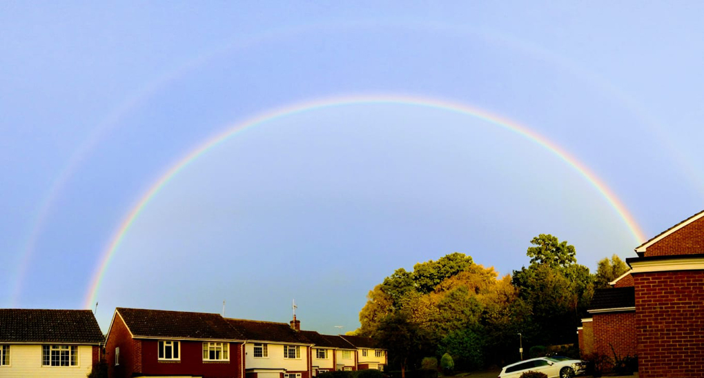 complete arch rainbow over houses