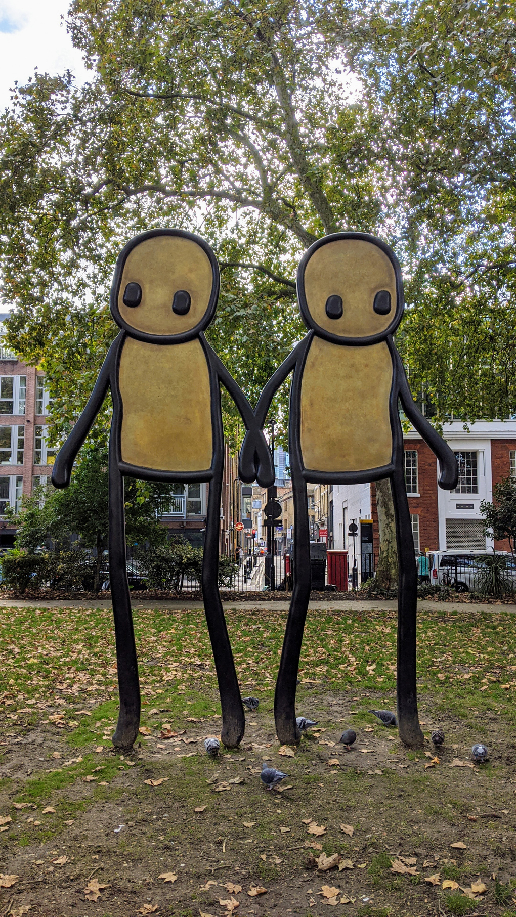 A tall sculpture of two stick figures holding hands.