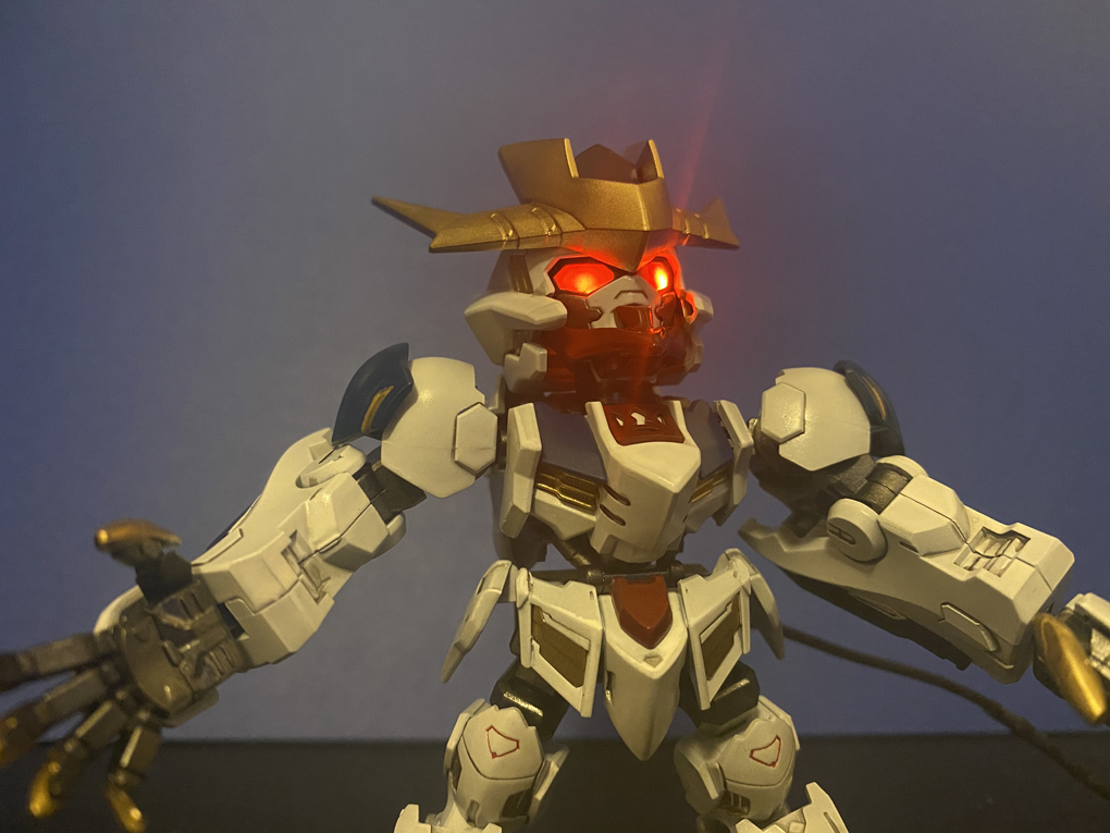 A Super Deformed Cross Silhouette Gundam Barbatos Lupus Rex, with custom paint job giving it deep reds, dark blues, gold claws, and LEDs lighting the eyes. The LEDs cause lens flare, making it look menacing.
